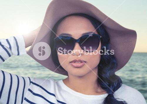 Composite image of Woman in summer hat against sea with flare