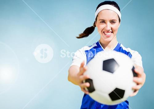 Composite image of a sports woman holding a foot ball against blue sky