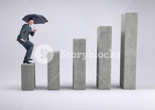 Composite image of Businessman standing on a graph post with an umbrella against grey background