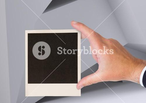 Composite image of Hand holding Polaroid photo against geometric background
