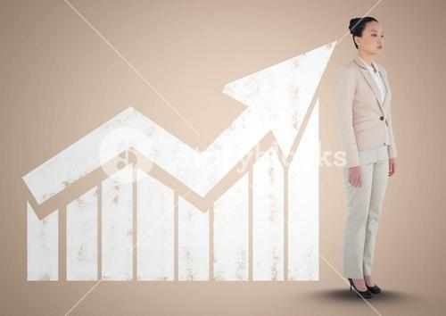 Businesswoman standing in front of graph against a neutral background