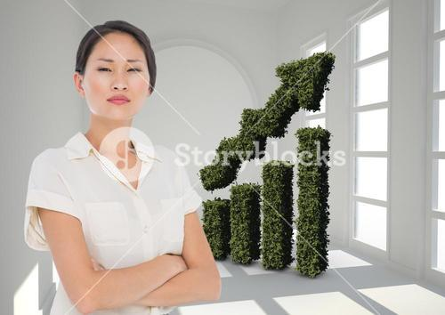 Businesswoman Standing in front of Graph against grey background