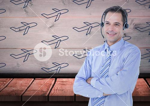 Travel agent with headset against a wood background with blue planes