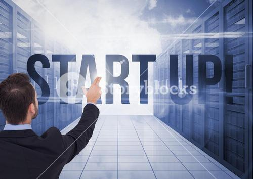 Businessman Standing pointing at Start Up Word against a blue background