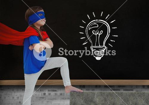 Super Hero kid and blackboard with lightbulb against a black background