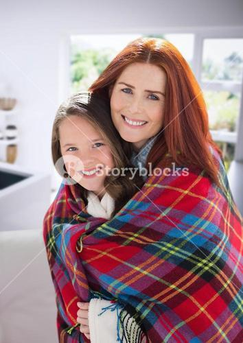 Mother and Daughter Hugging against a home background