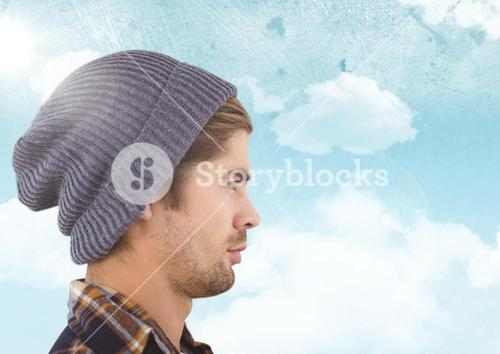 Man with beanie against sky with flare background
