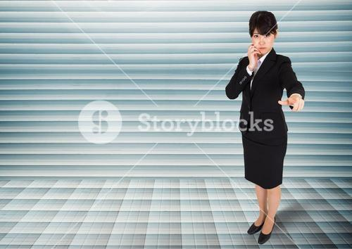Businesswoman looking and pointing at camera against grey background