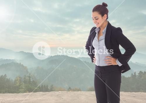 Businesswoman looking down against mountain background