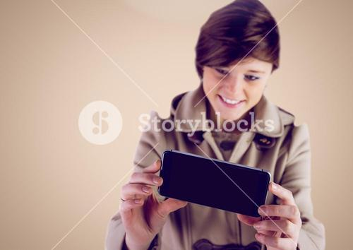 Woman using Phone against a neutral background