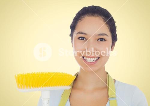 Happy Cleaner lady smiling at camera against a yellow background
