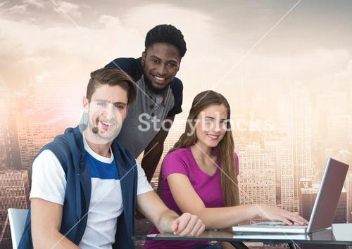 Group of friends using laptop and smiling against a city background