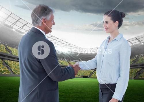 Business Man and woman at stadium shaking hands against a stadium background