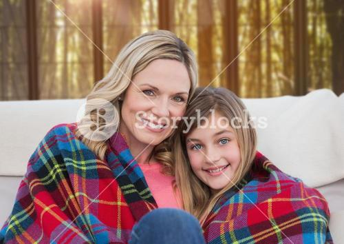 Mother and Daughter with blanket against a neutral background
