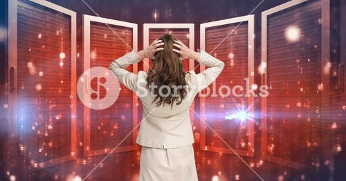Businesswoman Standing holding her head and looking at Graphic against red background
