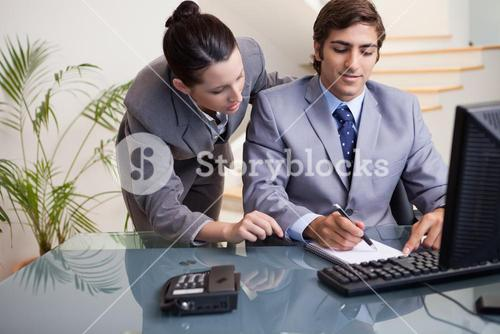 Businessman taking notes while getting mentored by colleague