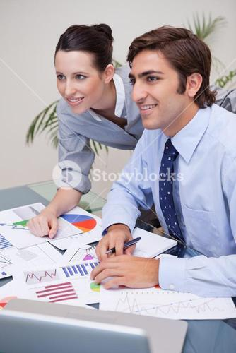 Smiling business team analyzing statistics together