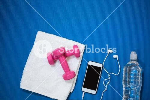 Mobile phone, water bottle, towel and dumbbell kept on exercise mat