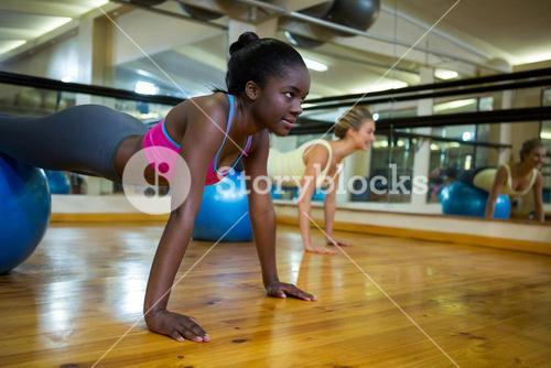 Woman doing pilates exercises on fitness ball with coach in fitness studio