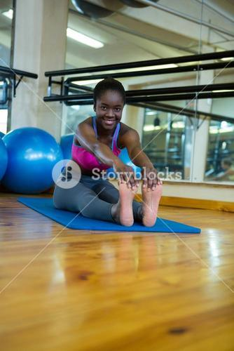 Portrait of smiling fit woman doing stretching exercise on mat