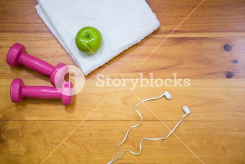 Gym equipment and apple kept on wooden floor