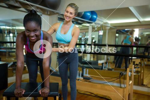 Portrait of trainer assisting woman with wunda chair in fitness studio