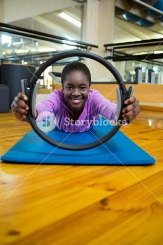 Portrait of fit woman exercising with pilates ring in fitness studio