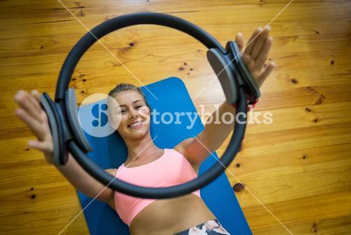 Smiling fit woman exercising with pilates ring on mat