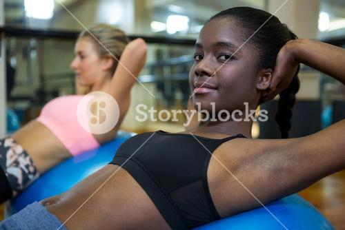 Portrait of smiling woman performing pilate on exercise ball
