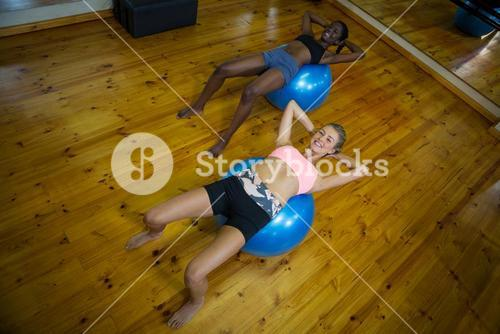 Two fit women performing pilate on exercise ball
