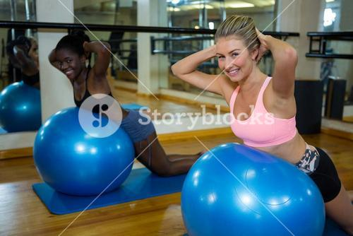 Two smiling women performing pilate on exercise ball