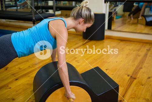 Fit woman doing pilates on arc barrel