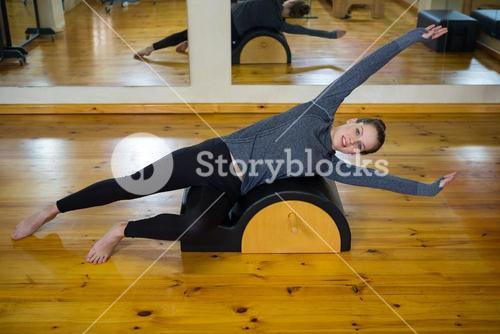 Portrait of beautiful woman exercising on arc barrel