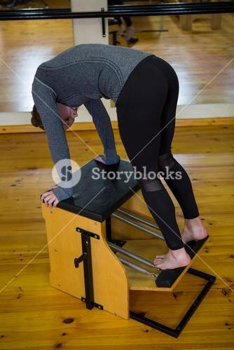 Determined woman exercising on wunda chair