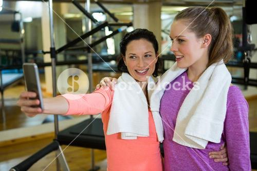 Beautiful fit women taking selfie on mobile phone after workout