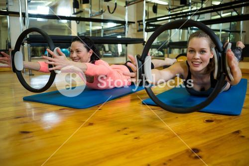 Fit women exercising with pilates ring