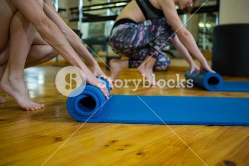 Fit women rolling up exercise mats after workout