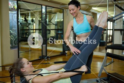 Female trainer assisting woman with stretching exercise