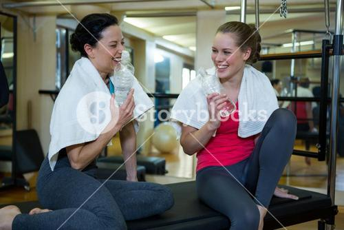 Happy women holding water bottle while relaxing after workout