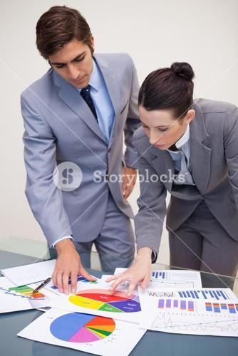 Business partners looking at statistics together