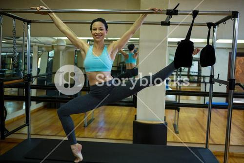 Portrait of happy woman performing stretching exercise on pilates cadillac