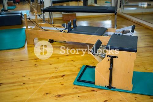 Reformer and wunda chair on wooden floor