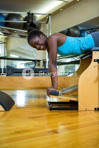 Portrait of happy woman exercising on wunda chair