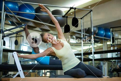 Determined woman practicing stretching exercise on reformer