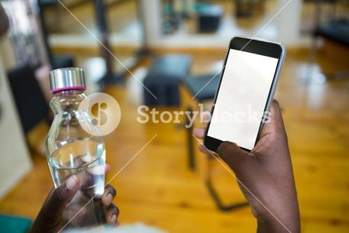 Woman holding water bottle and using mobile phone