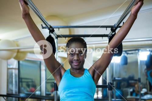 Portrait of beautiful woman performing stretching exercise on pilates cadillac