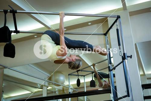 Determined woman performing stretching exercise on pilates cadillac