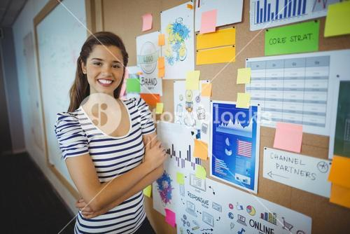 Portrait of female executive standing with arms crossed near bulletin board