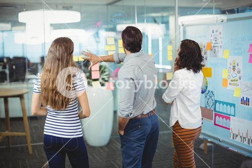 Team of executives discussing over sticky notes in office