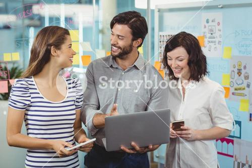 Team of executives discussing over laptop